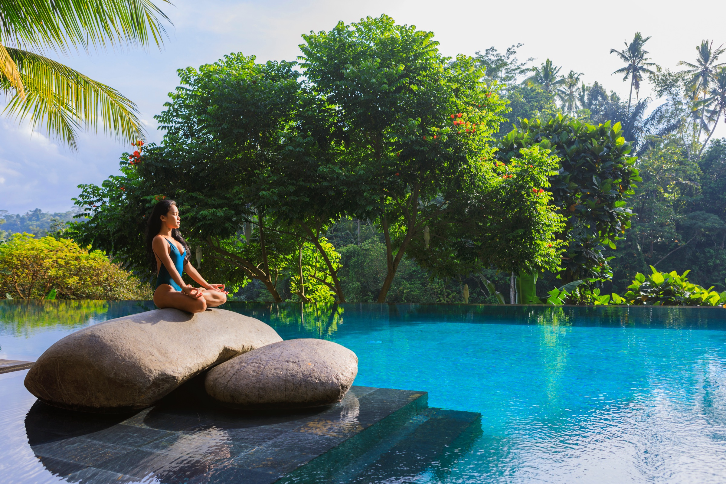 Yoga by a tropical pool setting.